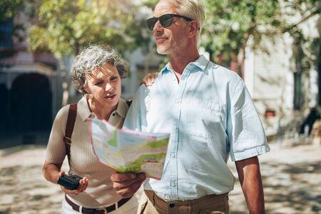 hombres maduros: matrimonios de edad de raza caucásica la lectura de un mapa de la ciudad y mirando a su alrededor. Pareja mayor uso de un mapa en unas vacaciones.