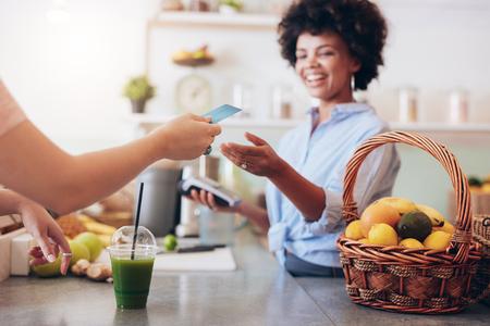 pagando: Disparo de un propietario sola barra de jugos de tomar el pago del cliente. Mujer al cliente el pago de jugo con tarjeta de crédito.
