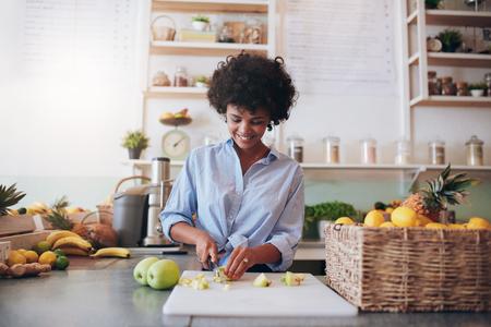 negocios comida: tiro bajo techo de fruta atractiva mujer joven de cortar para hacer un jugo fresco. femenino africano que trabaja en el bar de zumos.