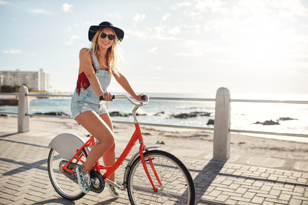 seaside: Happy young woman riding her bike at the waterfront. Stylish young female cycling on a seaside promenade on a summer day.