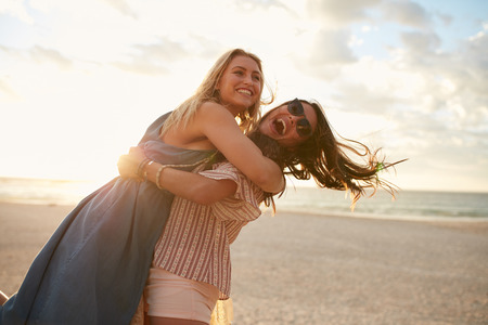 vacationers: Outdoor shot of young woman smiling and lifting her friend on a beach. Young women vacationers enjoying on the beach.