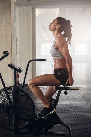 Side view shot of fitness woman spinning air bike at the gym. Fitness woman working out on exercise bike at the gym. Stock Photo