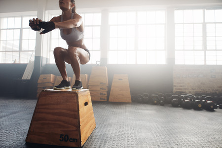 boxes: Shot of a young woman jumping onto a box as part of exercise routine. Fitness woman doing box jump workout at crossfit gym.