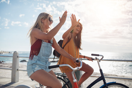 Female cycling on a summer day and giving each other a high five. Two young female friends riding their bicycles on the seaside promenade.