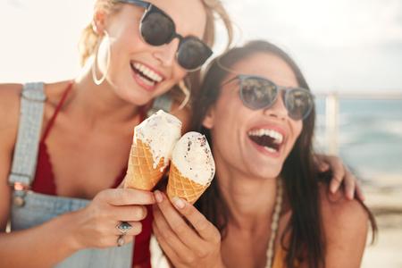 Dvě mladé kamarádky baví a jíst zmrzlinu. Veselá mladé ženy jíst zmrzlinu venku.