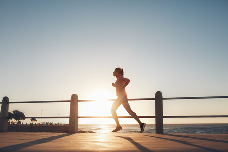 woman sunset: Silhouette of young woman running along the sea during sunset. Fitness woman jogging on a road by the sea. Stock Photo