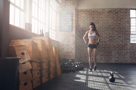 Full length image of fit young woman walking in the crossfit gym. Female athlete preparing herself before a intense training.