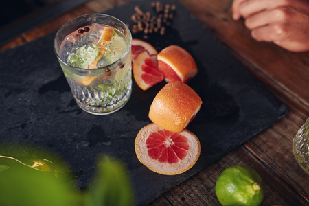 freshly prepared: Close up image of freshly prepared cocktail drink with grapefruit slices on table.