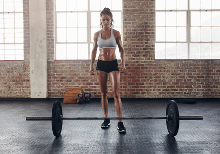 tough woman: Full length portrait of fit young woman standing at gym with barbells on floor. Tough crossfit female at gym.