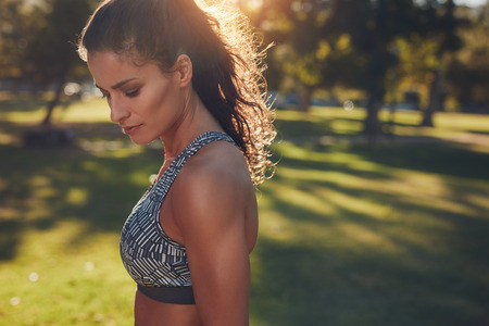 run down: Close up shot of fit young woman standing outdoors in a park. Muscular young woman in sportswear looking down.