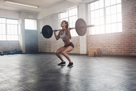 Female bodybuilder doing exercise with a heavy weight bar in gym. Full length shot of fitness woman practicing weightlifting at health club. Archivio Fotografico