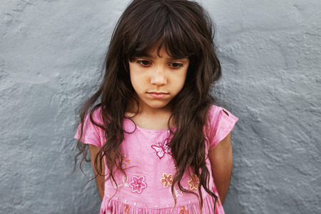 Close up portrait of little girl standing looking upset. Sad young girl standing against a grey wall. Stock Photo