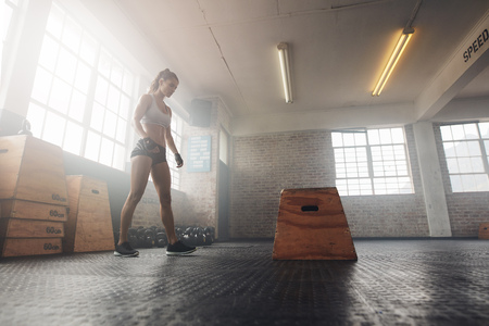 Shot of a muscular young woman working out with a box at the gym. Focused young female athlete standing by jump box at cross fit health center.