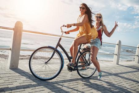 Zwei stilvolle junge weibliche Freunde auf einem Fahrrad am Meer entlang. Beste Freunde, die einen Tag auf dem Fahrrad zu genießen.