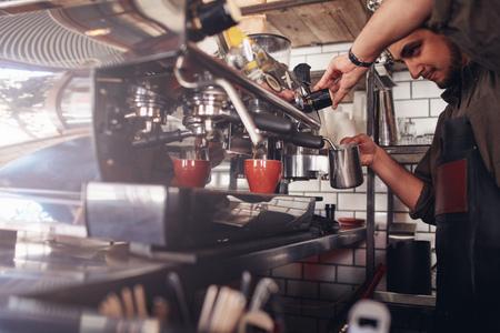 バリスタのコーヒー メーカーを使ってコーヒーのカップを作るのショット。カフェ労働者がコーヒーを準備します。
