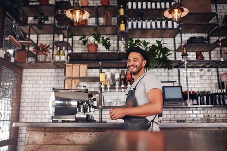 Indoor Schuss von glücklichen jungen Bar Besitzer an der Theke und Wegschauen lächelnd