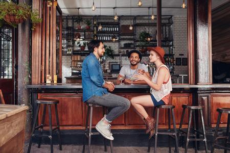 Retrato de feliz grupo de jóvenes reunidos en una tienda de café y hablar. Tres jóvenes amigos sentados en una mesa de café. Foto de archivo
