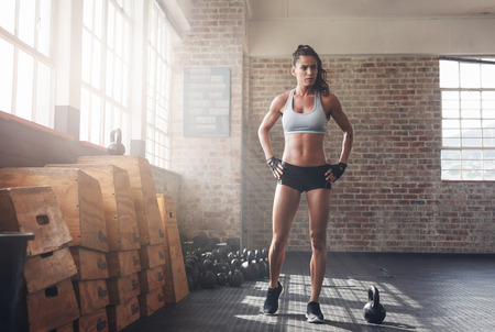 Full length shot of determined fitness woman walking in the crossfit gym. Muscular sportswoman warming up before a intense workout.