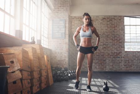 Pleine longueur de tir déterminée femme de remise en forme de marche dans le gymnase crossfit. sportswoman musculaire échauffement avant une séance d'entraînement intense. Banque d'images - 58716092