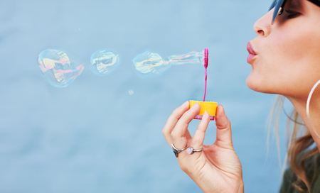 soap sud: Close up side view shot of young female model blowing soap bubbles on blue background. Focus on hands and wand.