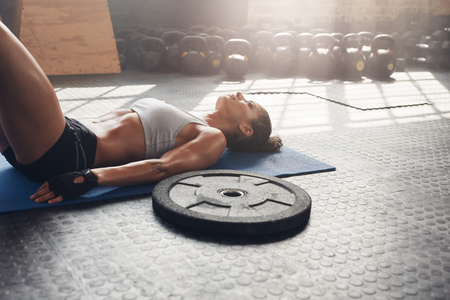 Fitness woman relaxing after her workout at gym. Heavy weight plate on floor with muscular woman lying on exercise mat.