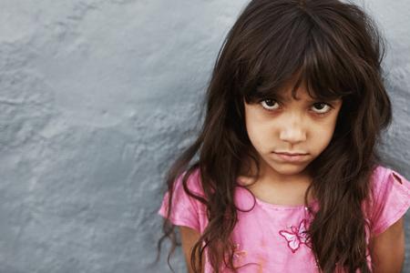 mignonne petite fille: Close up portrait d'une jeune fille préado avec une expression sérieuse debout sur fond gris. Femme enfant regardant la caméra.