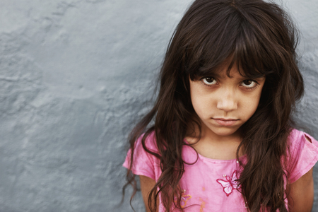 Close up portrait of preteen girl with serious expression standing against grey background. Female child staring at camera. Stock Photo