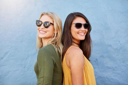 mujeres de espalda: Foto de dos mujeres jóvenes sonriendo espalda con espalda. amigos femeninos con estilo con gafas de sol contra el fondo azul.
