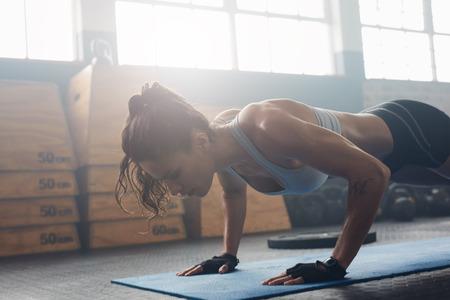 Schot van de jonge vrouw doet push-ups in de sportschool. Spier vrouw die opdrukoefeningen op oefening mat op gymnasium. Het vrouwelijke uitoefenen op fitness mat op gymnasium.
