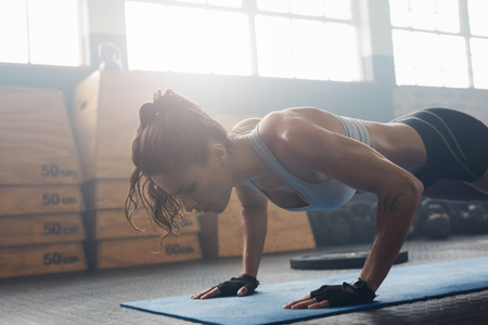 Shot of young woman doing push-ups at the gym. Muscular female doing pushups on exercise mat at gym. Female exercising on fitness mat at gym. Stock Photo - 58716600