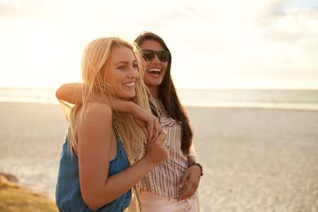 Two beautiful young women strolling on a beach. Female friends walking on the beach and laughing on a summer day, enjoying summer vacation.