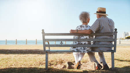 couple in summer: Rear view of loving senior couple relaxing at the seaside. Elderly man and woman sitting a bench outdoors.