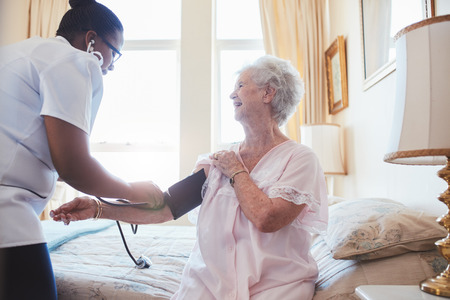 happy nurse: Nurse visiting senior female patient at home and taking blood pressure. Old woman sitting on bed. Stock Photo