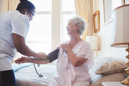 Zdravotní sestra na návštěvě starší pacientka doma a užívat krevní tlak. Stará žena sedí na posteli.