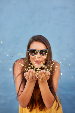 Portrait of happy young female model blowing confetti in the air over shining background