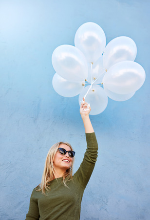joyous: Shot of joyous young female model with balloons. Caucasian woman in sunglasses against blue background.