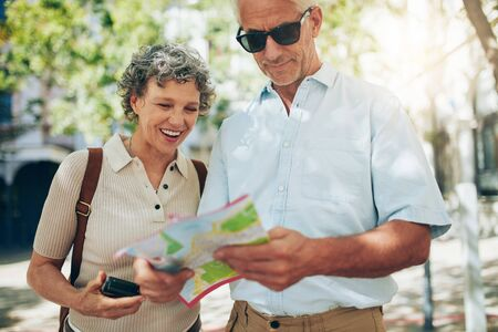 Senior couple on vacation reading a map. Mature man and woman looking for direction in foreign city. Фото со стока