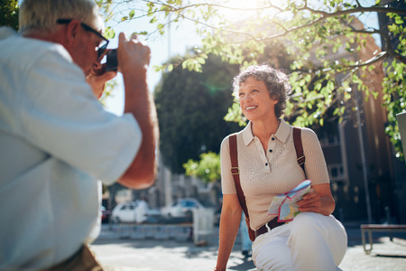 Senior man taking vacation photographs of his wife. Beautiful senior woman posing for camera while sitting outdoors on a bench in the city. Senior couple on vacation. Stock Photo