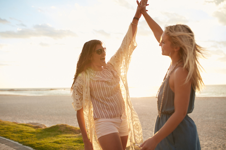 Two young women on the beach giving high five. Women friends enjoying beach vacation.