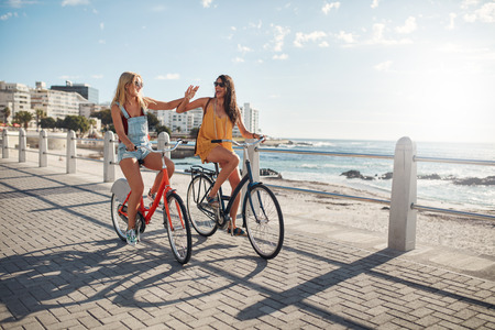 cycles: Two female friends riding cycles on the seaside promenade. Excited young women enjoying riding bicycles at the waterfront on a summer day. Stock Photo