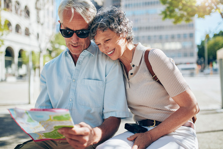 happy seniors: Happy mature couple looking at a city map. Two active seniors reading a map together while sitting outdoors on a bench.