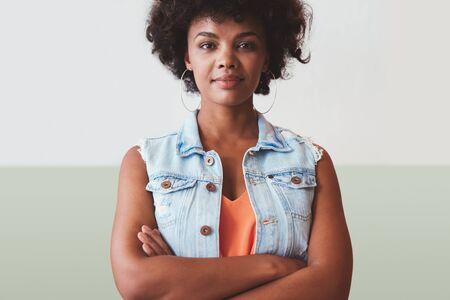 Portret van mooie jonge vrouw stond met haar armen gekruist tegen een muur. Zelfverzekerd jonge Afrikaanse vrouwelijke model in slimme casuals. Stockfoto