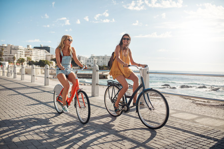Happy young female friends riding bicycles on the seaside road. Young women enjoying riding bikes at the waterfront on a summer day.