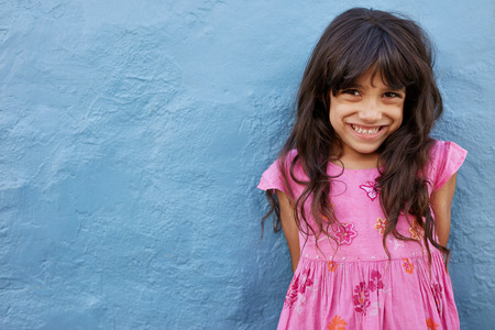 innocent: Portrait of cute little girl looking at camera and smiling while standing against blue wall. Innocent young female child with copy space.
