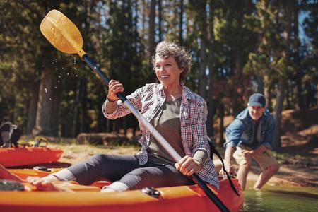 Portret van gelukkige hogere peddelen kajak in het meer met de mens ondersteunen van achteren. Ouder paar genieten van een dag op het meer.
