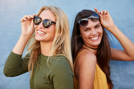 Pretty young female friends having fun. Both looking at camera and smiling against blue background.