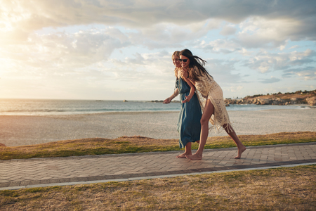best travel destinations: Full length shot of happy young women walking on a pathway along a beach. Best friends enjoying a walking along the sea shore. Stock Photo