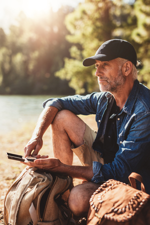 lost lake: Portrait of mature man with a compass sitting with backpack looking away at a view. Senior hiker sitting by a lake on summer day.