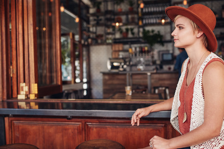side bar: Side view of beautiful young caucasian woman sitting at bar counter and looking away. She is wearing hat waiting for someone. Stock Photo
