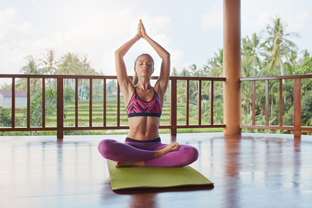 Horizontal shot of healthy and beautiful young woman sitting with joined hands at health center. Fit young female doing yoga workout.
